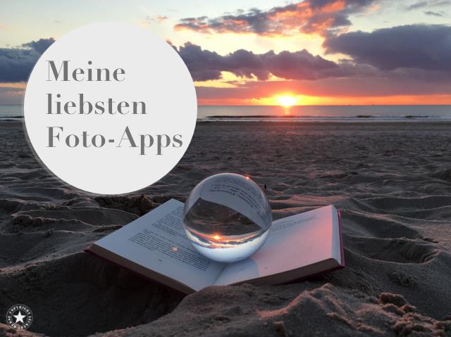 Buch und Glaskugel am Strand von Sylt